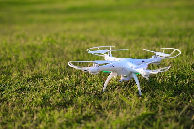緑の芝生に着陸する高解像度デジタルカメラを備えたドローンクワッドコプター。
