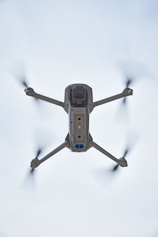 Дрон quadcopter с камерой, летящей в небе