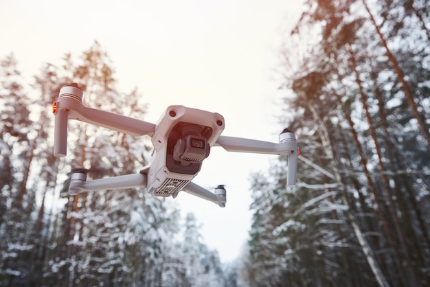 Дрон квадрокоптер с камерой, летящей в зимнем лесу