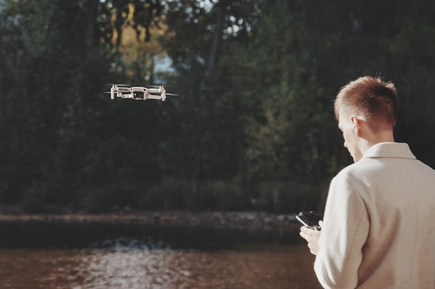 Drone quadrocopter controls off from man hands outdoors. young man releasing aerial copter to fly with small digital flying camera. concept of modern technology in our life. copy space for site
