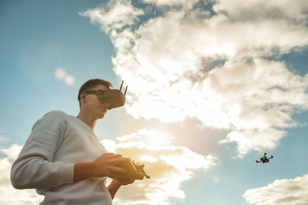 Drone quadrocopter flying, man operates in digital glasses hands outdoors. young man releasing aerial copter to fly with small flying camera. concept of modern technology in our life. copy space