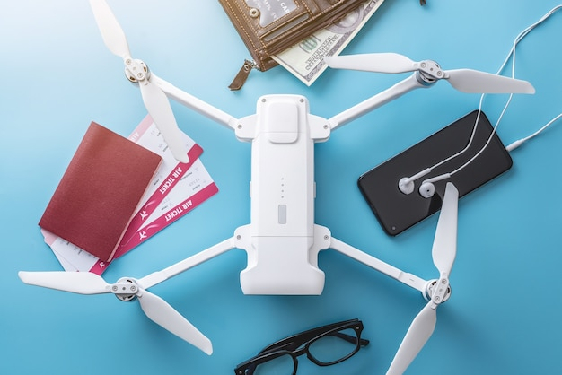 Drone quadrocopter and necessary things for flight. airline tickets, passport, money and phone with headphones on a blue background