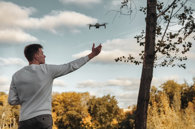 Drone quadrocopter taking off from man hands outdoors. young man releasing aerial copter to fly with small digital flying camera. concept of modern technology in our life. copy space for site