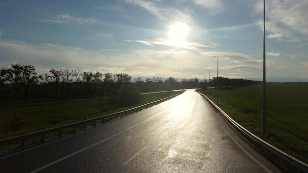 뿌린 들판 사이에 자동차를 위한 젖은 아스팔트 도로 위로 드론이 떠오른다
