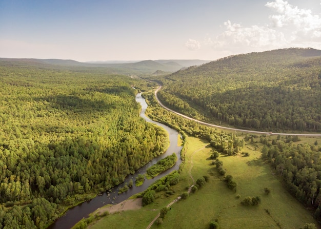 Drone over a river, country road and forest. aerial amazing view of streams, coniferous trees and hills. top nature landscape on a sunny day. water