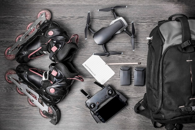 Drone and rollers, near a backpack and battery, with a leaf for planning, on a woody background, concept of portable quadrocopter