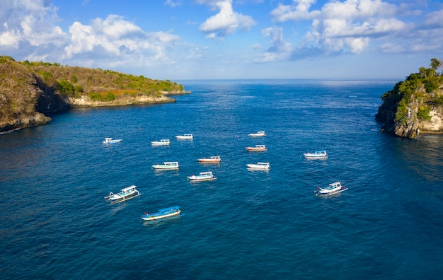 Drone shot of jukung boats at crystal bay at nusa penida, bali - indonesia.