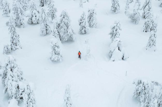 Снимок с дрона людей, идущих в снежном лесу в лапландии, финляндия