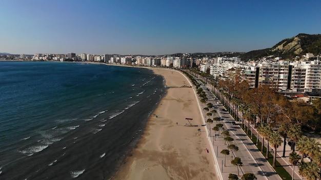 木々と青い水と明るい日にビーチのドローンショット