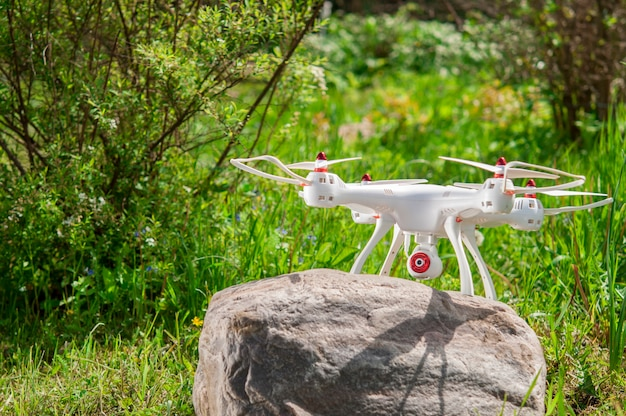 Drone standing on a large stone and prepared for takeoff.