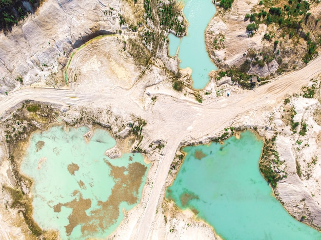 Drone view on a flooded kaolin quarry with turquoise water and white shore