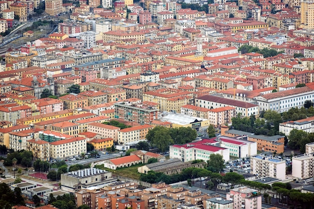 Drone view of many residential buildings with red roofs and lush trees located on streets of town