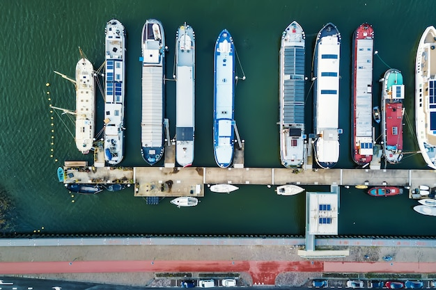 Drone view of modern barges and boats floating on sea water near quay in city