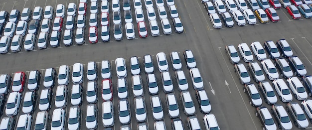 Drone view, new car parking, near the car dealer's logistics center. the parking lot of the updated lineup of cars near the auto shop.