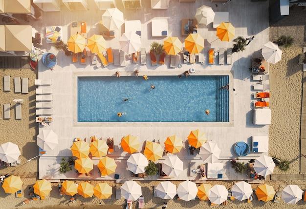 Вид с дрона на людей, расслабляющихся в бассейне с