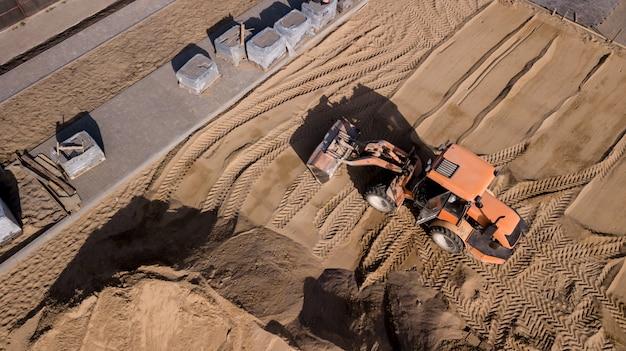農村景観におけるトラック、掘削機、道路修理作業のドローンビュー。ドローン写真。