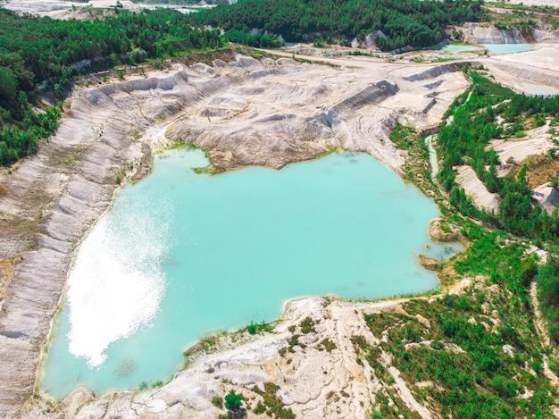青緑色の水と白い海岸の浸水カオリン採石場のドローンビュー