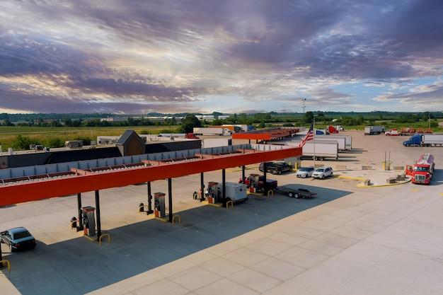 무인 항공기는 미국 고속도로의 주유소에서 도로 세미 트럭 위의 대형 자동차를 봅니다.