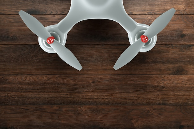 Drone, white quadrocopter on wooden, brown background with copy space. top view, flat lay