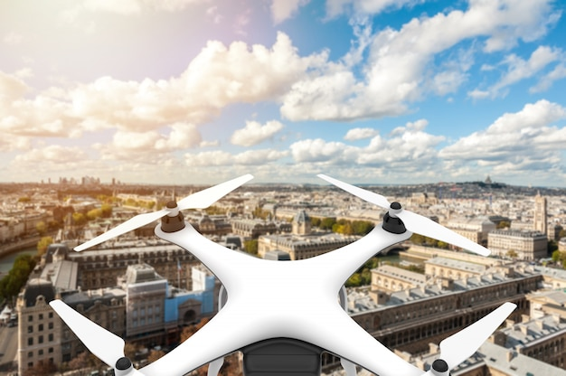 Drone with digital camera flying over a city with blue sky