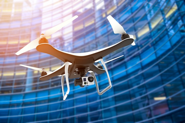 Drone with digital camera flying in front of modern skyscraper