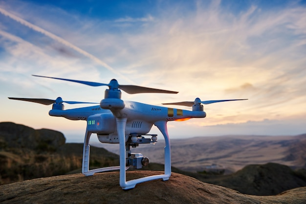 Drone with high resolution digital camera ready to fly at sunset in