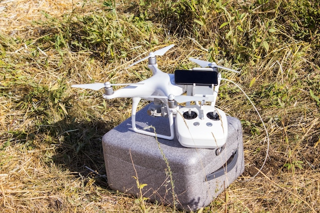 Drone with a mobile phone and remote control in the field
