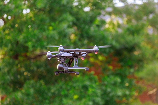 Drone with professional cinema camera flying over summer park.