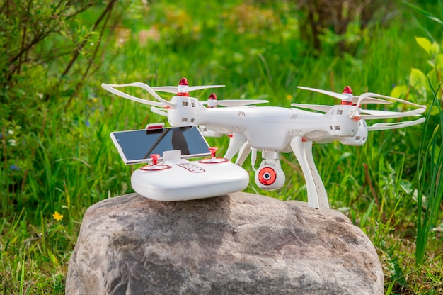 Drone with remote control on a background of nature.
