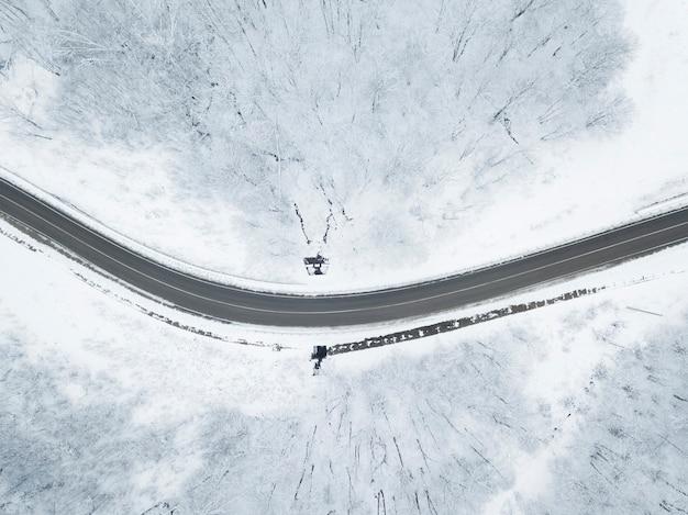 Drones eye view - зимняя извилистая дорога с высокогорного перевала на юге россии. отличное путешествие по густому лесу.