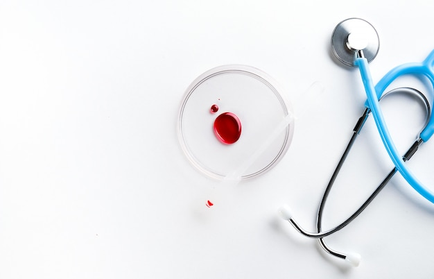 A drop of blood in a glass petri dish. next to it is a stethoscope.