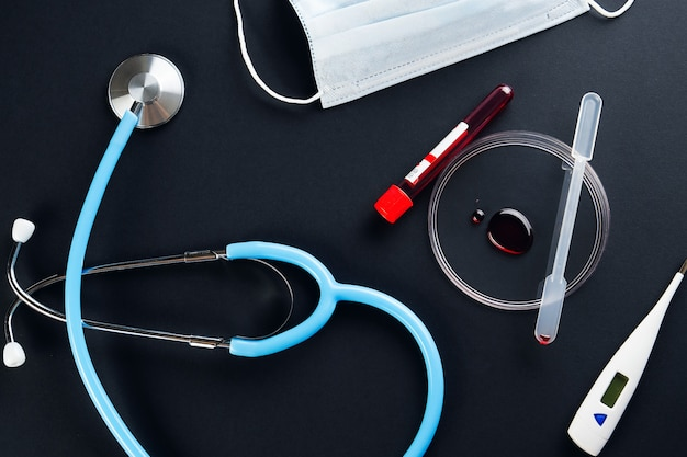 Drop of blood in glass petri dish, test tube with blood sample, thermometer, disposable mask and stethoscope