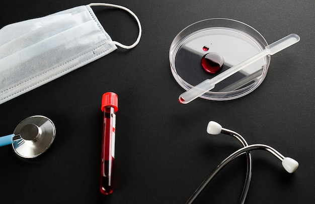 Drop of blood in a glass petri dish, test tube with medical sample, medical mask and stethoscope