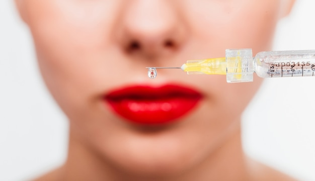 A drop of botox hangs from the needle of the syringe against the face of the patient