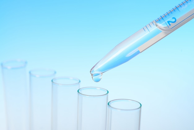 Drop from pipette falling in a tube, text space