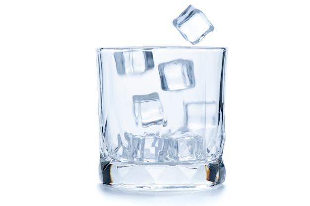 Бросьте кубики льда в пустой рок-бокал или старомодное стекло на белом фоне, концепция стеклянной посуды