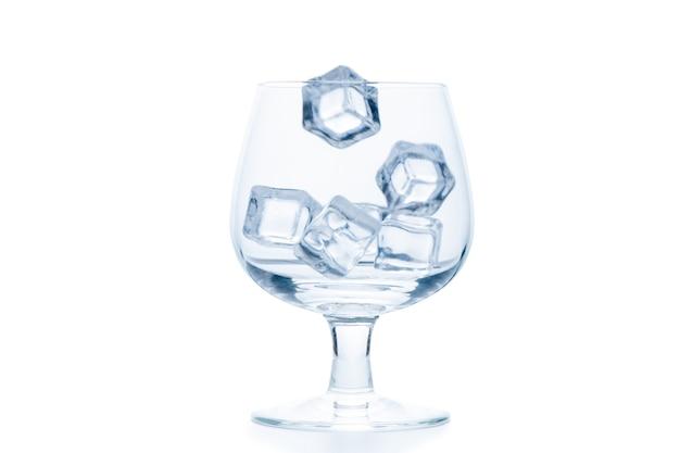 Бросьте кубики льда в пустой стаканчик для рюмок или воздушный шар, изолированные на белом фоне, концепция напитка