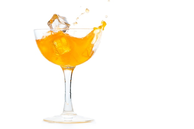 Бросьте кубики льда в апельсиновую газировку в стакане маргариты, изолированном на белом фоне, концепция летнего напитка