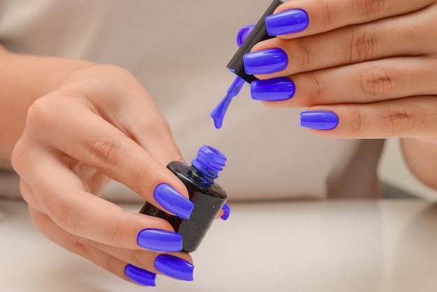 A drop of nail polish drips from the edge of the brush closeup female hands hold blue nail polis