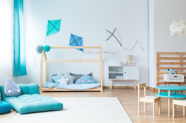 벽에 파란색 연이 있는 다채로운 어린이 침실의 흰색 카펫에 파란색 매트리스에 모양의 베개를 떨어뜨립니다.