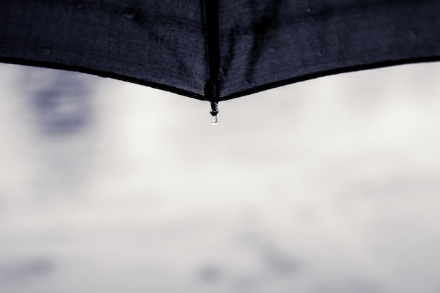 Drop of water falls from the umbrella during the rain. umbrella protects against bad weather