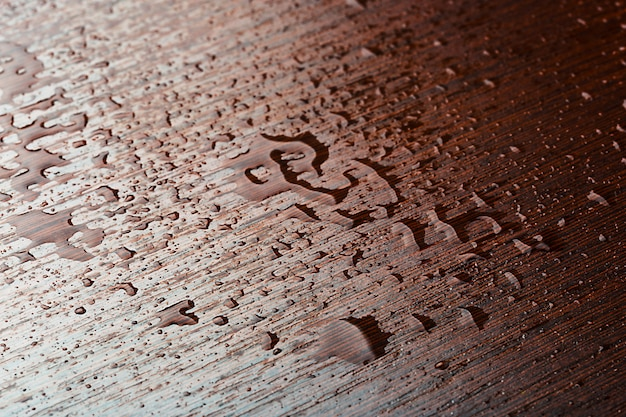 Drop of water on wooden table, close-up