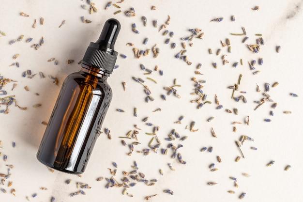 Бутылка-капельница эфирного масла лаванды, разбросанные цветы сушеных фиолетовых цветов лаванды на мраморном столе.