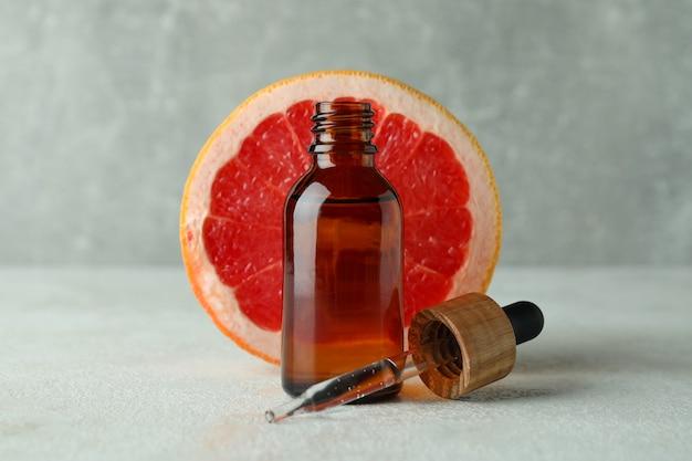 Бутылка капельницы с маслом и грейпфрутом на белом текстурированном столе