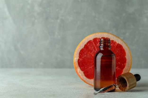 白いテクスチャテーブルにオイルとグレープフルーツのスポイトボトル