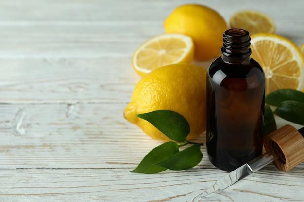 Бутылка-капельница с маслом и лимонами на белом деревянном столе