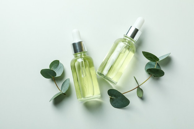 Dropper bottles of eucalyptus oil and twigs on white background
