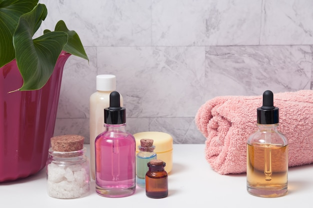 Dropper bottles of tincture, salt, oil or serum, a towel and a plant in the bathroom. skin care spa concept