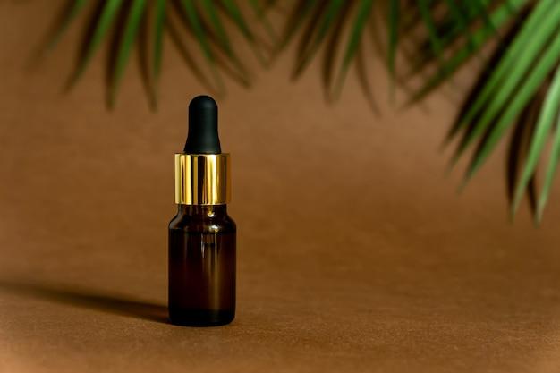 Флакон-капельница из темного стекла с пипеткой или капелькой. макет essential liquid. модный фон с тропическими листьями и копией пространства
