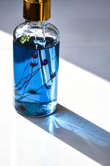 Макет стеклянной бутылки капельница. крупным планом капельница с маслом каннабиса cbd, используемым в медицинских целях. масло марихуаны cbd на белом фоне, глубокие тени, засушенные цветы внутри